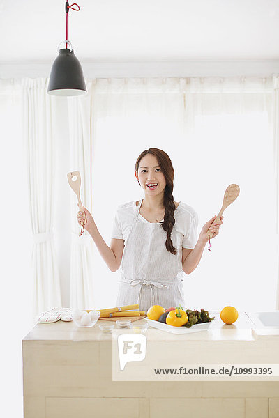 Young attractive Japanese woman cooking at home