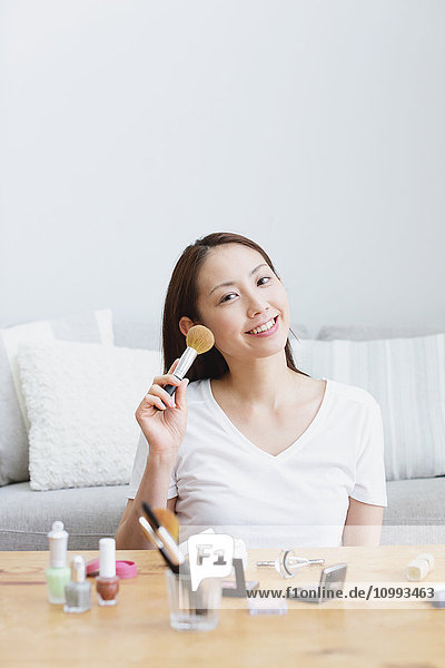Young attractive Japanese woman doing her make-up at home