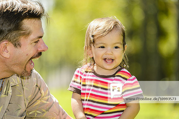 Kid and dad playing in a city park