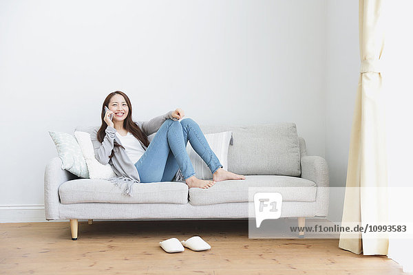 Young attractive Japanese woman on the phone on the sofa