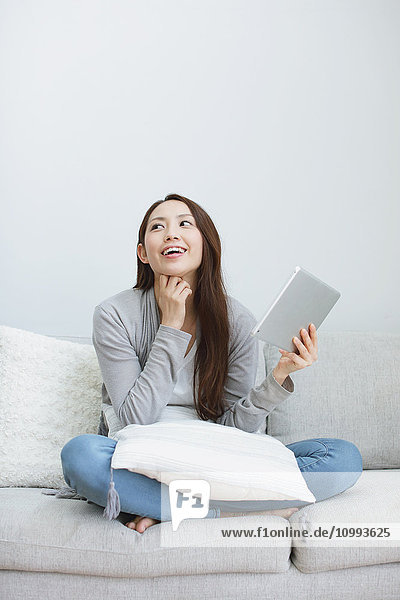 Young attractive Japanese woman with tablet on the sofa