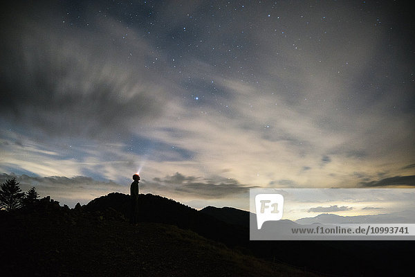 Caucasian man with torch on in the mountains at night