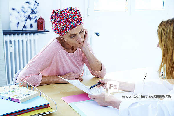 Woman suffering from cancer talking to her doctor.