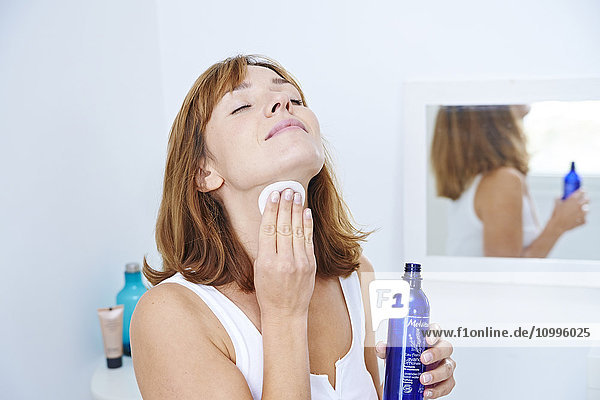 Woman applying lavender floral water on her face.
