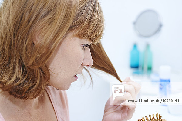 Woman inspecting the tip of her hair.