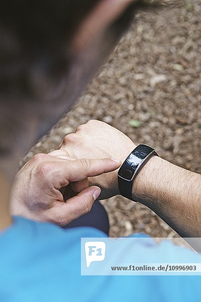 Man checking his connected bracelet.