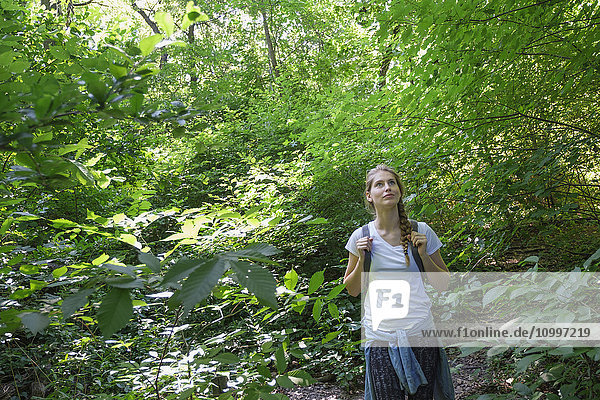Young woman standing in woodlands