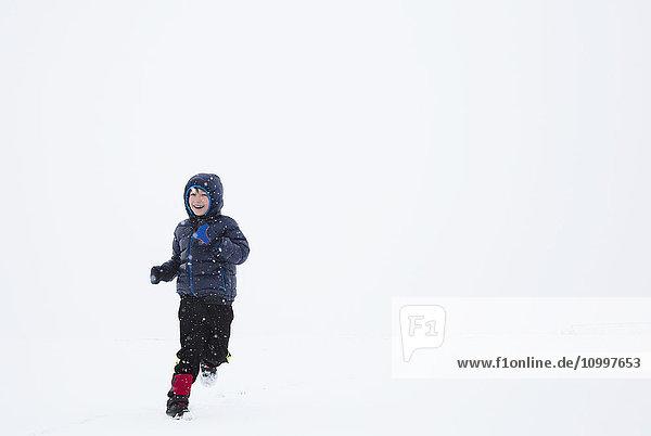 Boy (6-7) running in snow