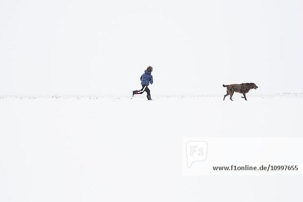 Boy (6-7) running with dog