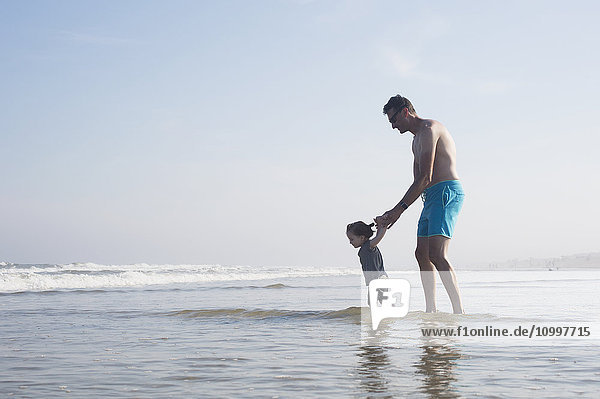 Father with daughter (18-23 months) wading in sea