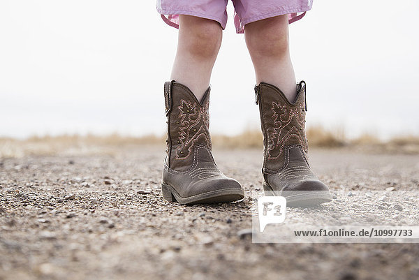 Low section of baby girl (18-23 months) wearing cowboy boots