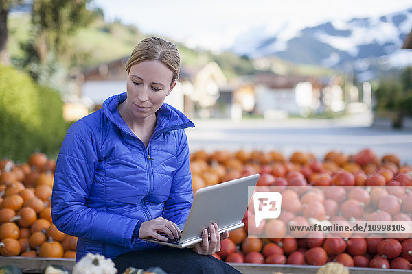 Austria  Salzburger Land  Maria Alm  Mature woman in blue jacket using laptop in market stall