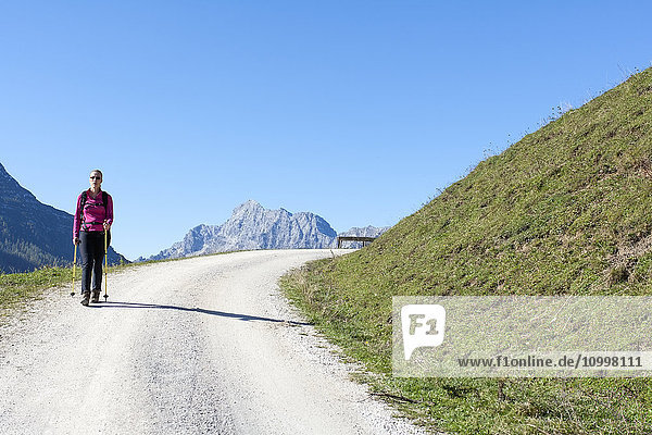 Austria  Salzburger Land  Weissbach  Mature woman hiking on sunny day in mountain landscape