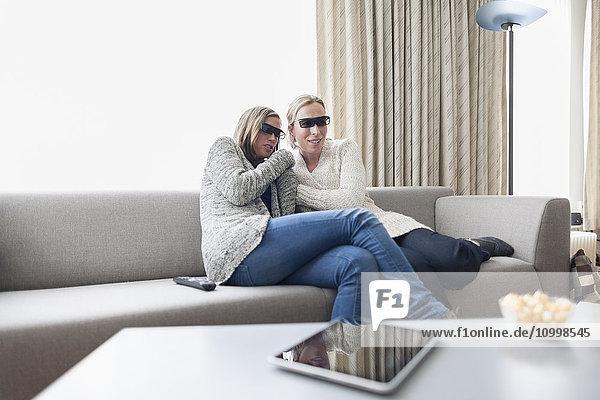 Women in 3d glasses sitting on sofa in living room