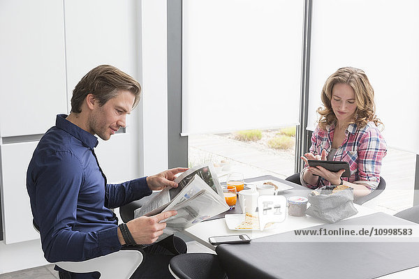 Mid-adult couple reading newspaper and using tablet at breakfast table