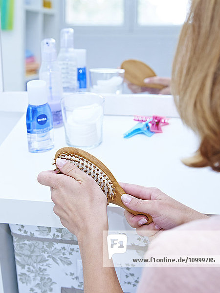 Woman removing hair from her brush.