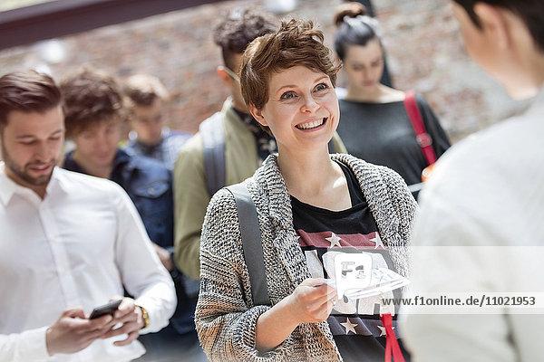 Lächelnde junge Frau mit Referenzen auf der Technologiekonferenz