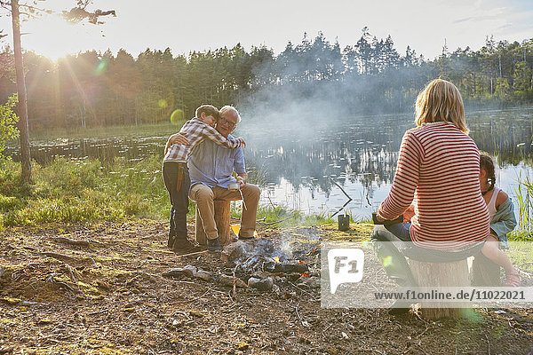 Großeltern und Enkelkinder umarmen sich am Lagerfeuer am sonnigen Seeufer.