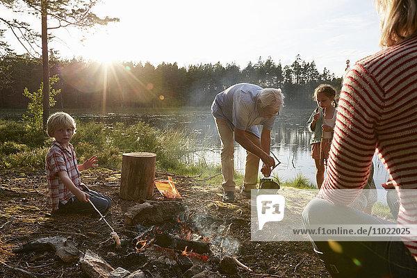 Großeltern und Enkelkinder am Lagerfeuer am sonnigen Seeufer im Wald