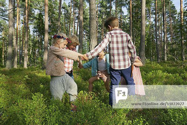 Jungen und Mädchen halten ihre Hände im Kreis zwischen Bäumen im Wald.