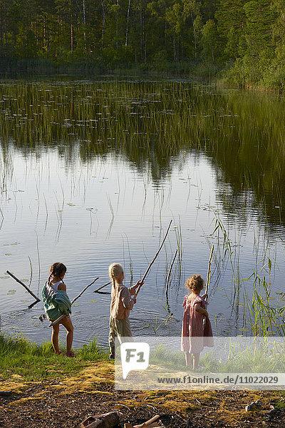 Mädchen fischen am sonnigen Seeufer