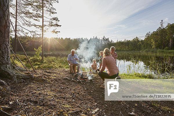 Großeltern und Enkelkinder beim Lagerfeuer am sonnigen Seeufer im Wald