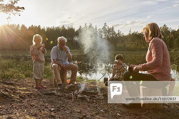 Großeltern und Enkelkinder am Lagerfeuer am sonnigen Seeufer