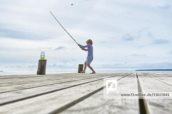 Junge beim Angeln am Seeufer