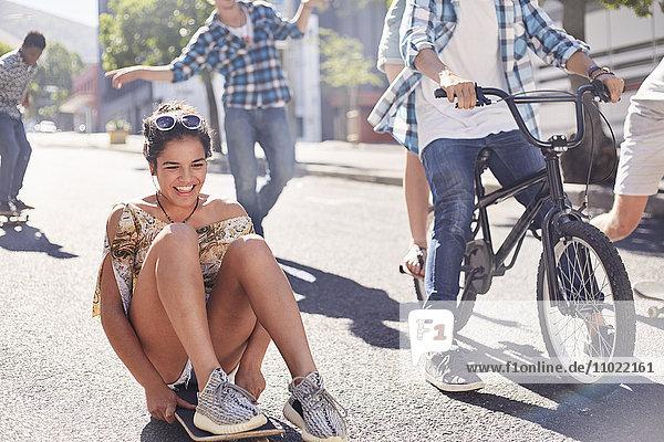 Begeisterte Teenagerin beim Skateboarden mit Freunden auf der sonnigen Stadtstraße