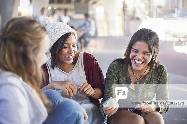 Teenage girls with cell phone laughing and hanging out