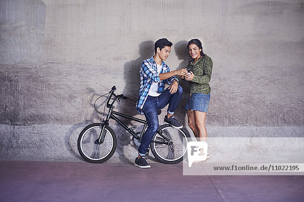 Teenager-Paar mit BMX-Fahrrad SMS an der Wand