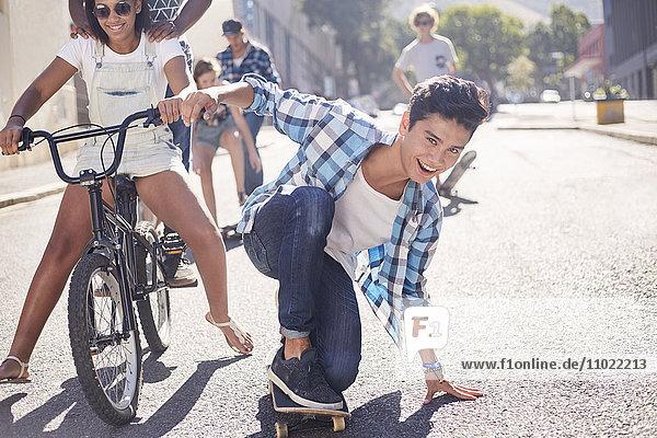 Porträt lächelnder Teenager mit Freunden auf der sonnigen Stadtstraße