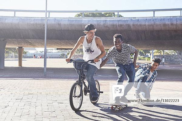 Teenager Jungen fahren BMX Fahrrad und Skateboarden im sonnigen Skatepark
