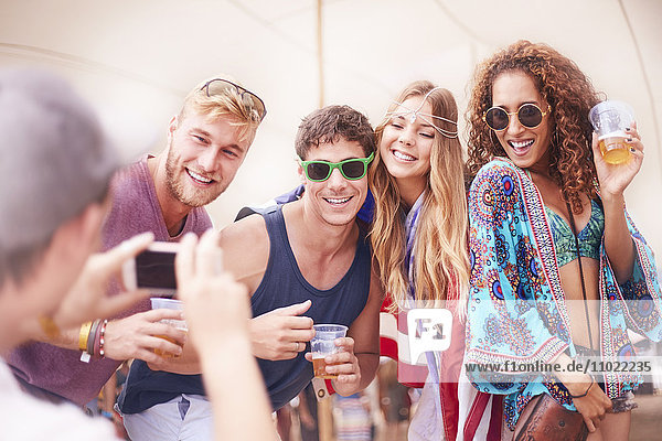Young friends with beer posing for camera phone at music festival