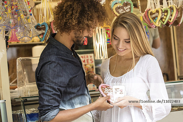 Young man gifting his girl friens with a gingerbread heart