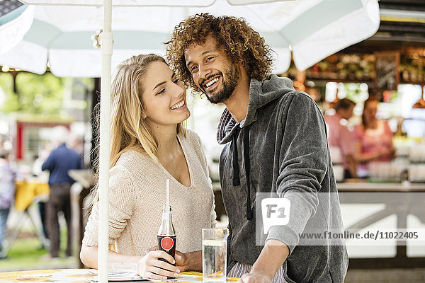 Young couple drinking beverage at a fun fair food stand
