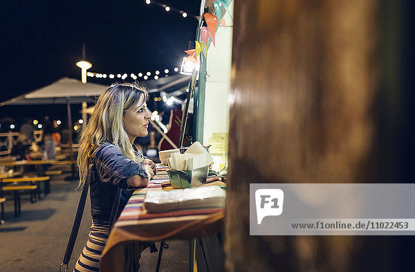 Young woman waiting in front of food stall at summer night festival