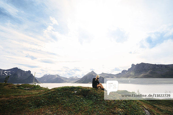 Woman photographing while sitting on mountain by lake