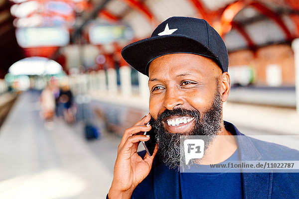 Happy businessman using mobile phone at railroad station