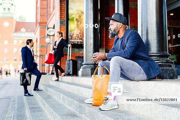 Thoughtful businessman sitting on steps outside railroad station