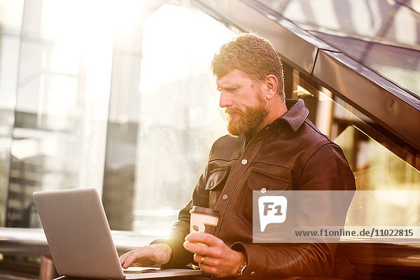 Businessman using laptop while sitting outside railroad station