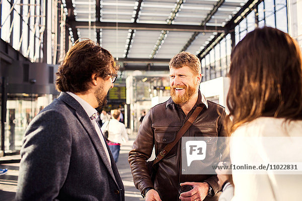 Happy businessman discussing with colleagues at railroad station
