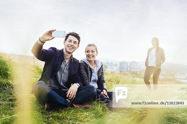 Happy friends taking selfie while sitting on grassy hill