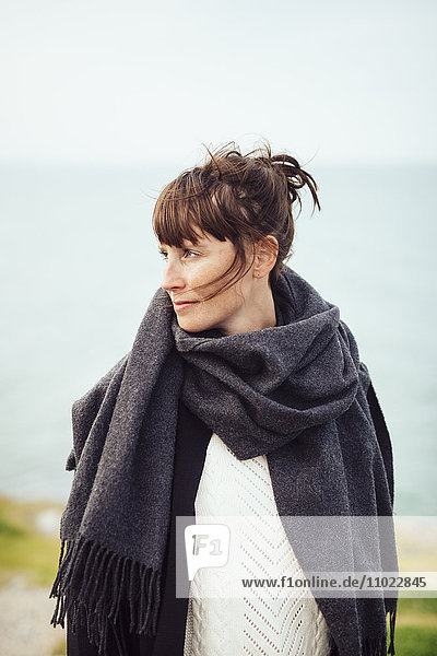 Mid adult woman looking away at beach