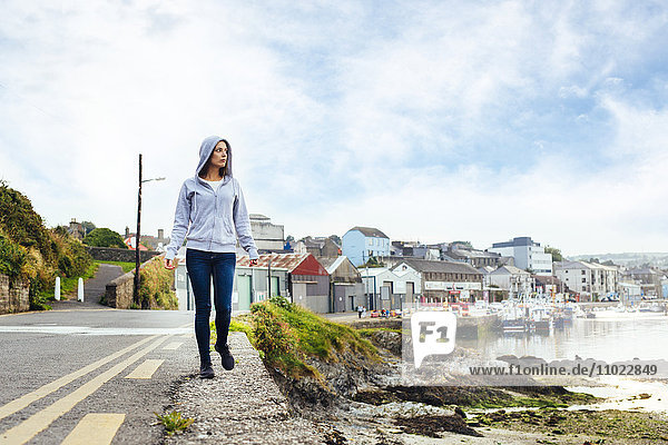 Full length of woman walking on road by harbor
