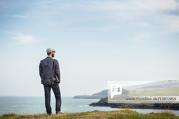 Rear view of man looking at view while standing on hill