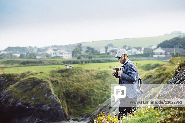 Side view of man photographing on hill