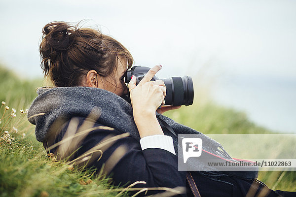 Side view of woman photographing through SLR camera on hill