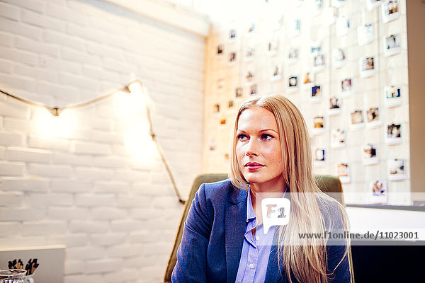 Thoughtful young businesswoman looking away in creative office