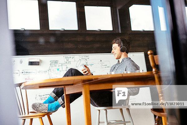 Happy businessman listening music through smart phone in office